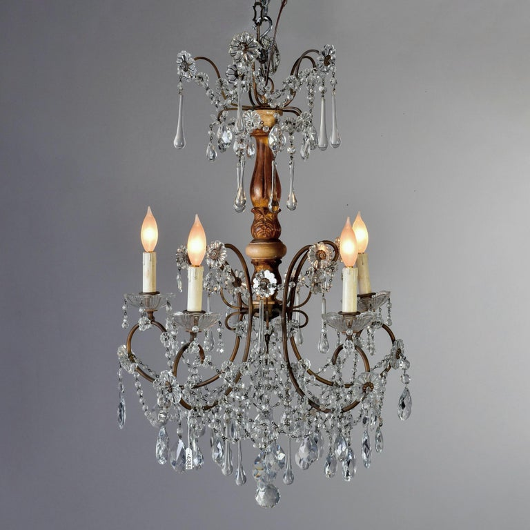 Italian crystal chandelier with gilded wood center support has five candle style lights and crystal flowers, long drops, beaded swag and faceted pendants, circa 1920s. New wiring for US electrical standards.