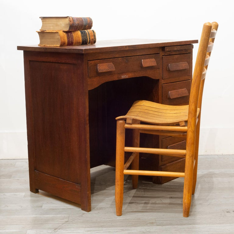 About  An original Oak children's writing desk with one large drawer, four side drawers and pull out tray. The desk features include a unique locking mechanism. To unlock the four side drawers, the main drawer must be pulled out.   Contact us for