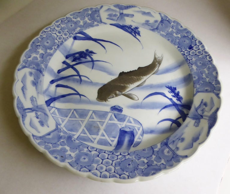 Beautiful and unusual blue and white antique Japanese Imari Charger depicting a dark colored Koi swimming among the reeds close to a stylized pier, early 20th century. Appropriate firing marks centered on back and underglaze Japanese mark. Very good