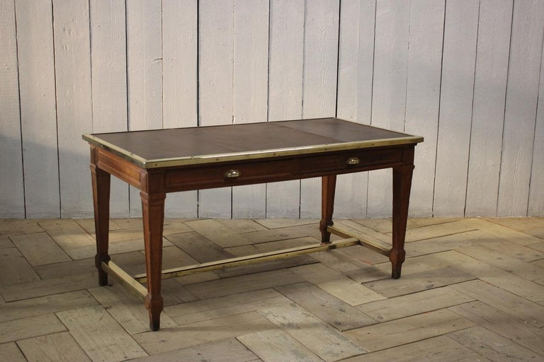 A good quality, early 20th century French Bank of France desk in oak, with the original brass stretcher and mounts. The top with new tan leather.