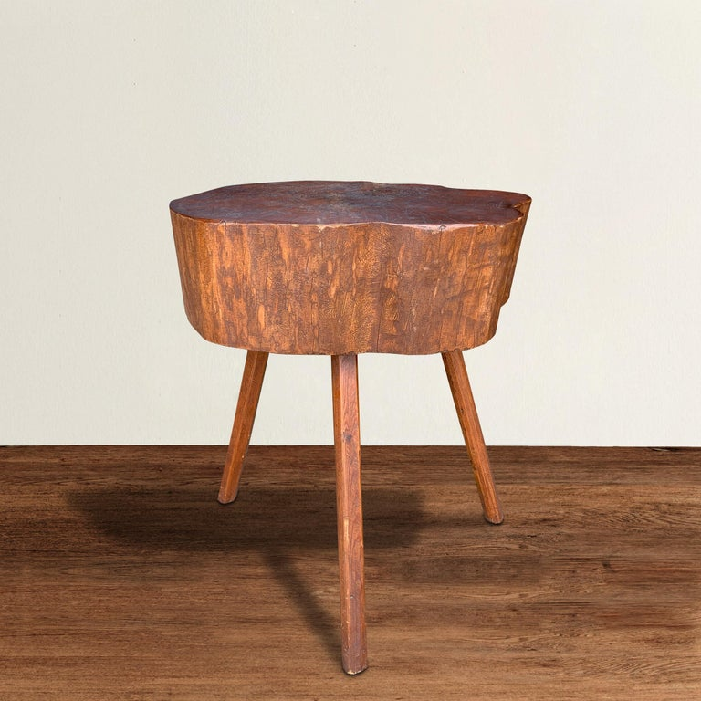 A quaint early 20th century American Primitive butcher block table made from a sliced log, with a beautiful stained dark red finish on top, and pine stick legs. Perfect as a pedestal, side table next to a sofa, or a bedside table. Could also be cut