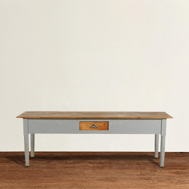 A wonderful early 20th century American maple farm table with an unfinished top, and gray painted sides and turned legs, and single drawer in the center with an iron bin pull handle. This table has been used for generations in a kitchen and has a
