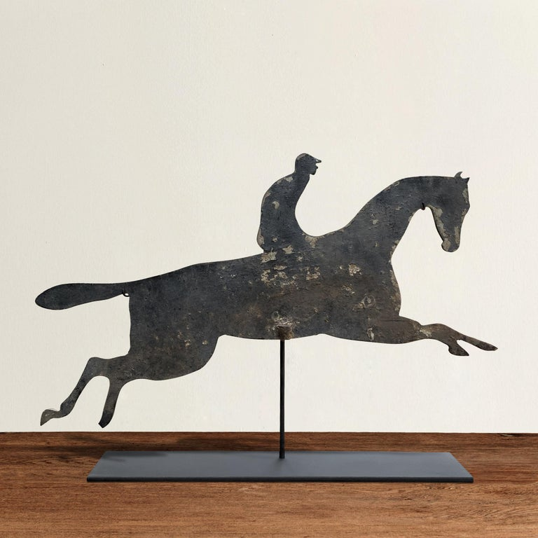 A fun and whimsical early 20th century American aluminum horse and jockey silhouette weathervane mounted on custom steel stand. Traces of original gray paint remain.