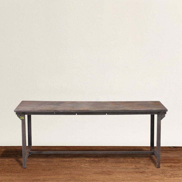 A wonderful and strong early 20th century American industrial steel work table with straight legs, a simple steel stretchers running between each pair of legs, and single piece of steel on top. Table can easily seat six people comfortably, or eight
