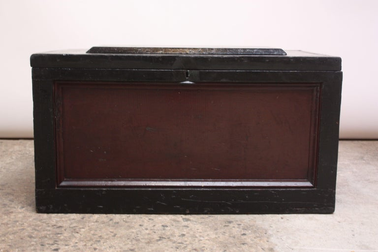 Wooden trunk / storage chest in maroon and black with a hinged top that opens to reveal three, removable boxes for storage. These boxes, vintage but later additions, can be removed for open storage. Solid brass hardware notes the date of manufacture