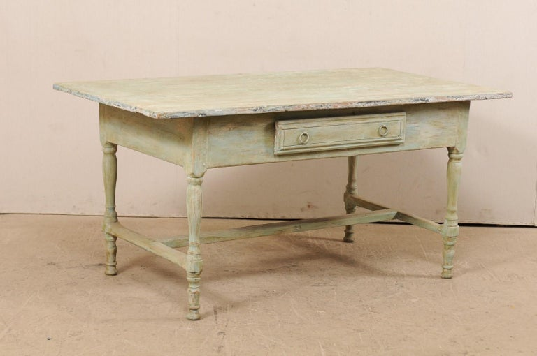 A Swedish painted wood table with single drawer from the early 20th century. This antique table from Sweden has a rectangular-shaped top that overhangs the plain, yet deep skirt beneath which houses a centre of one of the longer sides. It is raised