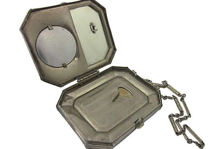 Art Deco silvertone metal compact featuring a yellow and blue guilloche enamel lid with a yellow rose motif. The back is a solid dark blue enamel. Inside is an area that used to hold blush, a powder holding section, and a mirror. The 9