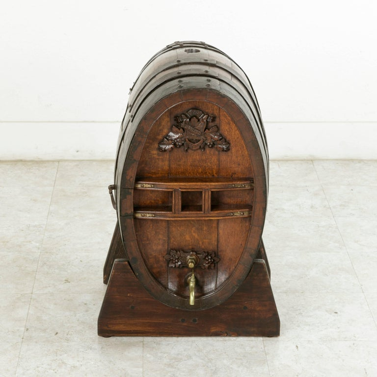This early 20th century artisan-made oak barrel was originally used for calvados, a regional specialty apple brandy in Normandy, France. Resting on a wooden stand, this barrel features a hand carved shield and banner surrounded by grape leaves and