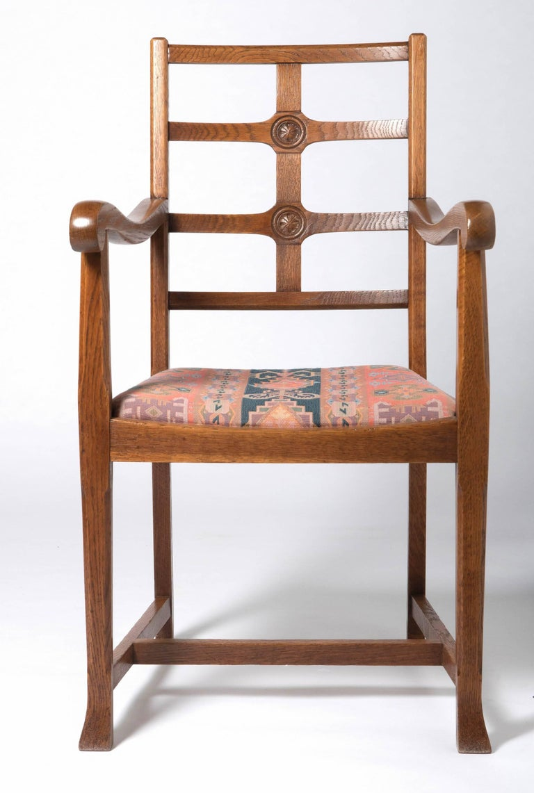 An early 20th century Arts & Crafts oak framed elbow chair, in the manner of Heals. The lattice back with 2 carved rosettes. The drop in seat raised on chamfered block legs. Measures: H 97 cm, W 54 cm, 43 cm, seat 46 cm England, circa 1920.