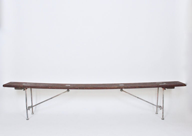 Long, folding, painted hickory and bronze bench from the Staten Island Ferry. Sturdy, narrow Hickory seat with oxblood red paint and locking, salt water patinated bronze legs. Latches fold and lock legs. Bench folds flat. Used on the Staten Island