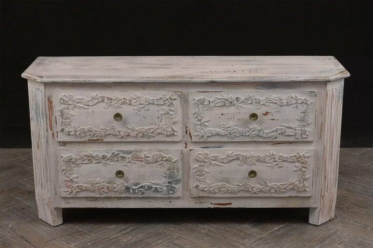 This 1920s Italian chest of drawers is one of a kind, the beveled wooden top and wooden frame have recently been painted in an oyster and red color combination with a beautiful distressed finish. On the facades of the four drawers there are floral