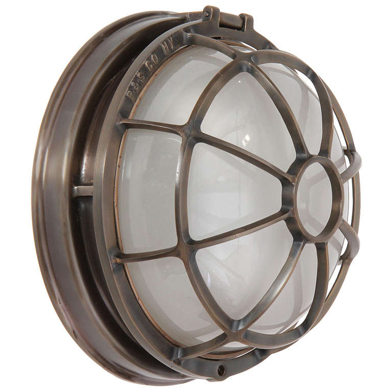 An excellent cast bronze sconce or ceiling mount lamp with two sockets underneath a glass dome protected by a well designed bronze cage.