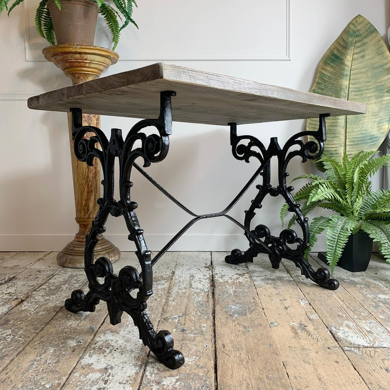 A beautifully cast table, dating to the early 20th century, the legs have been recently refurbished in black, and the top is a bespoke wood worker made thick reclaimed pine, finished in a specially formulated grey-silver wood stain, which blends
