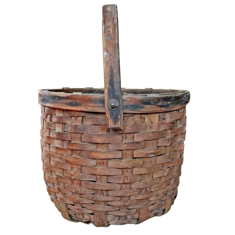 A wonderful early 20th century American handwoven cedar splint gathering basket with a swivel handle attached with bolts, and a heavy double band rim. Found in Wisconsin.