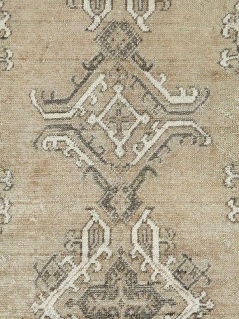 An antique Turkish Oushak carpet handmade during the early 20th century with an overall neutral and earth tone palette primarily in champagne, old ivory, and brown.