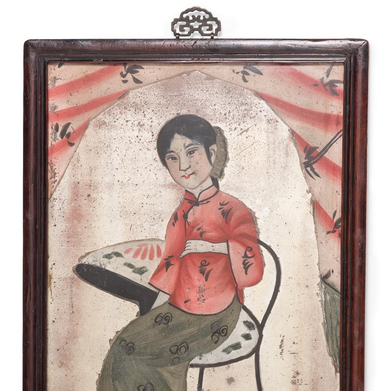 With its sparkling color and folk art appeal, this portrait painting from circa 1900 makes a delightful accent to a bedroom or study. This portrait painting of a young woman is an example of reverse glass painting, in which an artist applies paint