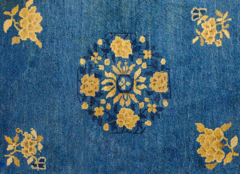 A wonderful early 20th century Chinese Art Deco rug with a central peony and chrysanthemum medallion woven in cream, ivory, and dark indigo set against a lighter indigo field of more peonies. The border contains a floral and scrolling vine partnered