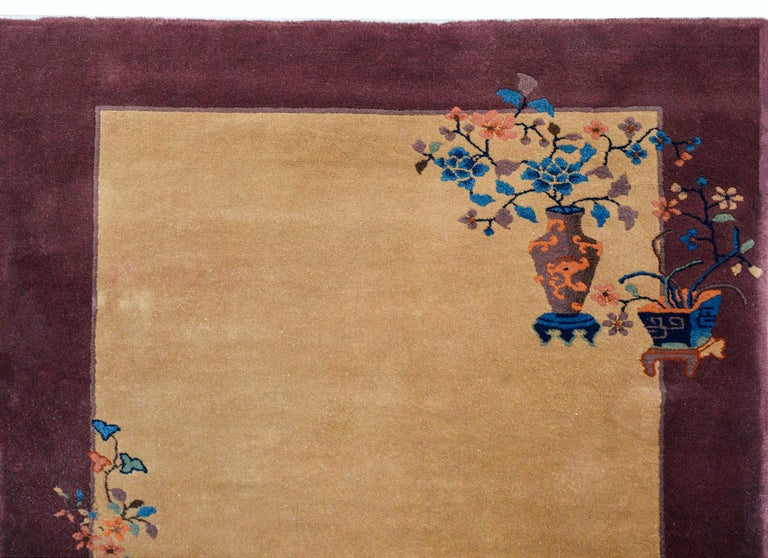 A wonderful early 20th century Chinese Art Deco rug with a beautiful solid beige background with a wide purple border, and overlaid with multi-colored auspicious flowers including peonies and cherry blossoms and potted vases sprinkled across the