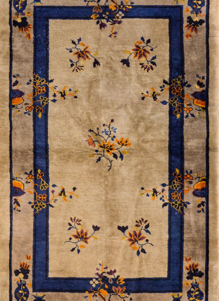 A wonderful early 20th century Chinese Art Deco rug with a gray background and thin indigo recessed border. Vases and clusters of auspicious flowers woven in orange, violet, and indigo surround the field.