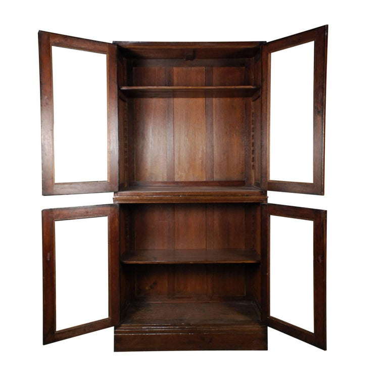 This early 20th century teak cabinet from the Northern Chinese port city of Tianjin has strong colonial influences from the Europeans living there at that time. It was likely designed with very shallow depth to accommodate books. The glass in the