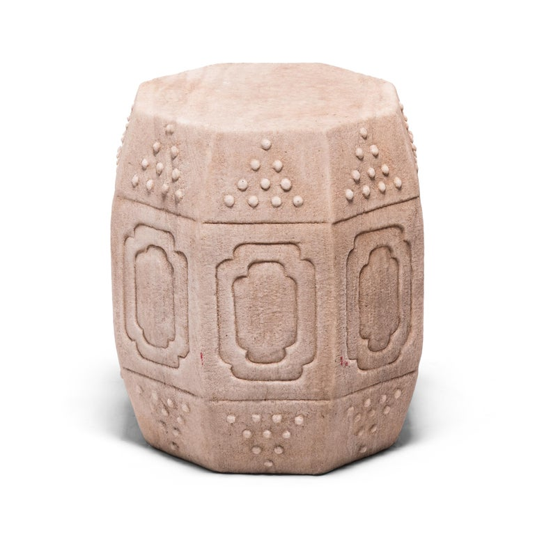 Hand carved of solid marble, this early 20th century drum-form stool has eight sides, an auspicious number symbolizing good fortune and prosperity. Each side is decorated with a simple yet effective design of nested cartouche panels and imitation