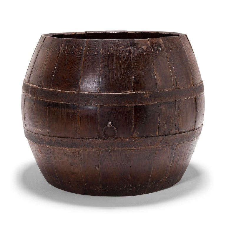 This squat, melon-like barrel is actually a turn of the century Peking opera drum, originally used by a theater troupe to accompany the dances and songs of traditional Chinese opera. The drum's finely joined oakwood slats are held together by