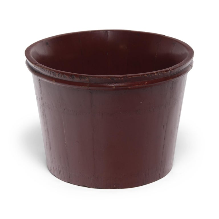 Layers and layers of glossy red lacquer render this water pail made of pine slats nearly seamless, giving it a sleek, burnished appearance. Once used to tote water, we find the vessel's timeless form and rich patina the perfect planter for lush