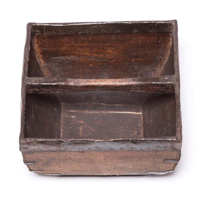 This rustic container was made over a hundred years ago to measure and hold a dou of rice, an ancient Chinese measurement. It is handcrafted with dovetail joints, iron-finished edges, and a hand-arched handle. An unusual amount of care was taken by