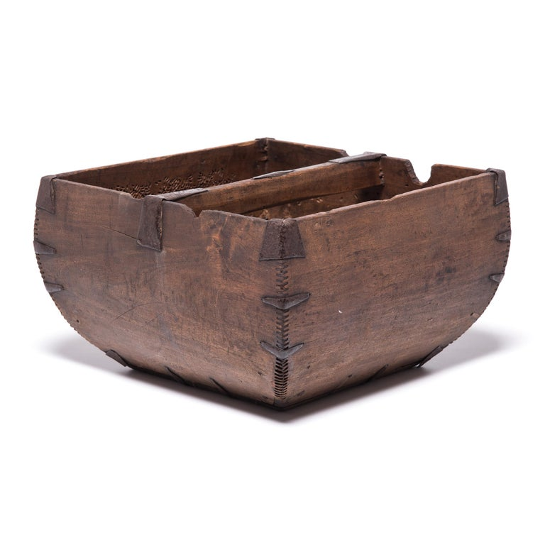 This rustic container was made over a hundred years ago to measure and hold a dou of rice, an ancient Chinese measurement. Hand-crafted with dovetail joints, the vessel has gracefully swelling sides and an arched handle, burnished from years of use.