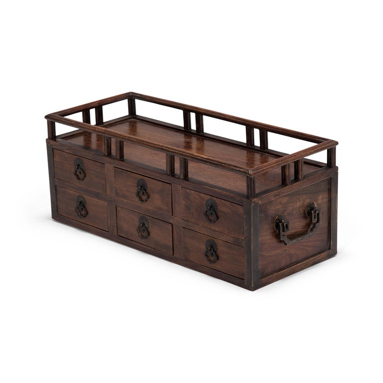 Crafted of fine rosewood, this early 20th century scholars' chest is an example of the multifunctional boxes used tabletop in lieu of a chest of drawers. While some were used to store cosmetics, jewelry, documents, and other accessories, the small