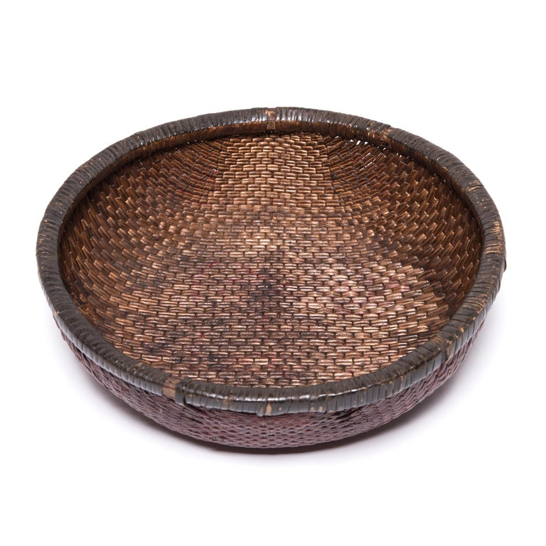 Tightly woven of natural reeds, this neat basket likely contained offerings of food, money, and fruit presented as part of ritual ancestor worship on a family altar. Over the course of the past century, the basket's deep color has developed
