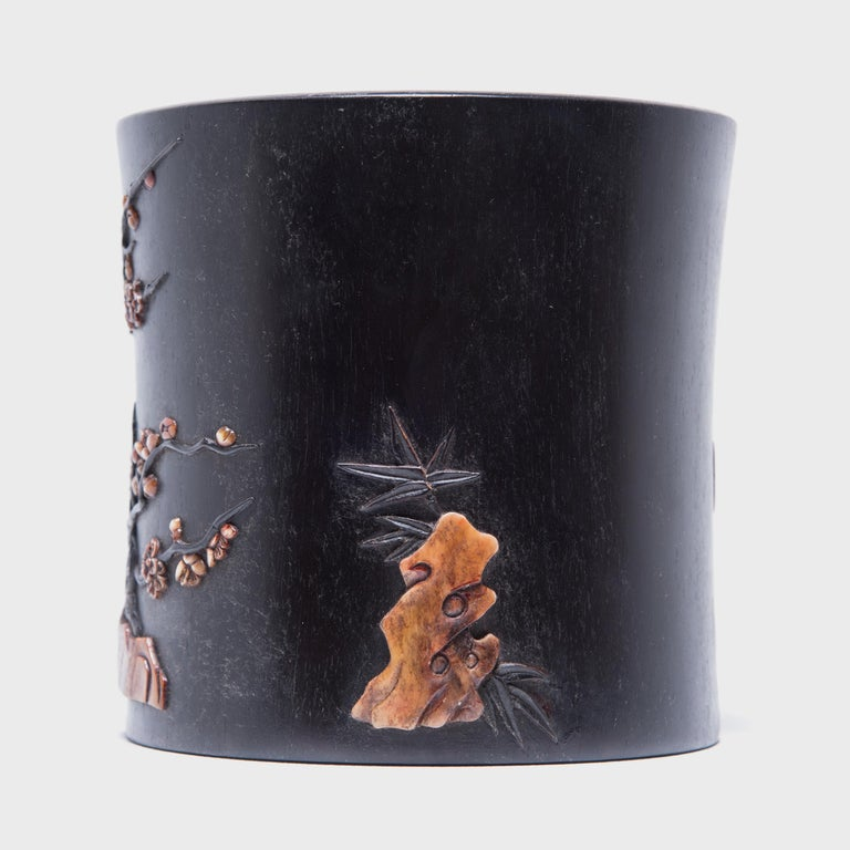 A brush pot or bitong, such as this one, was often found among a scholar's brushes, inkpot, and inkstone. This beautiful example is carved from zitan, a highly prized rare and slow-growing hardwood. Mother of pearl and soapstone inlays embellish the