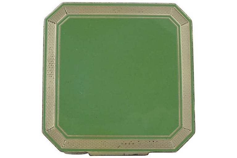 Art Deco sterling silver compact featuring a square green enamel center with an engine-turned frame and back. The compact opens to a mirror (crack on corner) and an interior powder compartment. Retains the original screen and a pink puff (which is