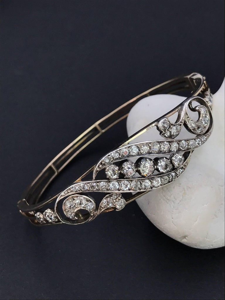 An early 20th century gold, diamond hinged bangle. Set in 9ct gold and silver. The old-cut diamond scrolling foliate motif, to the openwork half-bangle. Estimated total diamond weight 2.30cts. Inner diameter 5.7cms. Weight 14.6gms. Diamonds fairly