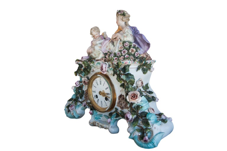 Early 20th century Dresden Porcelain clock depicting reclining woman in a bed of roses having Eros, the deity of love reading sheet music to her, trying to inspire her to play her harp that lies at her side. Very good condition. Tiny minute chips on