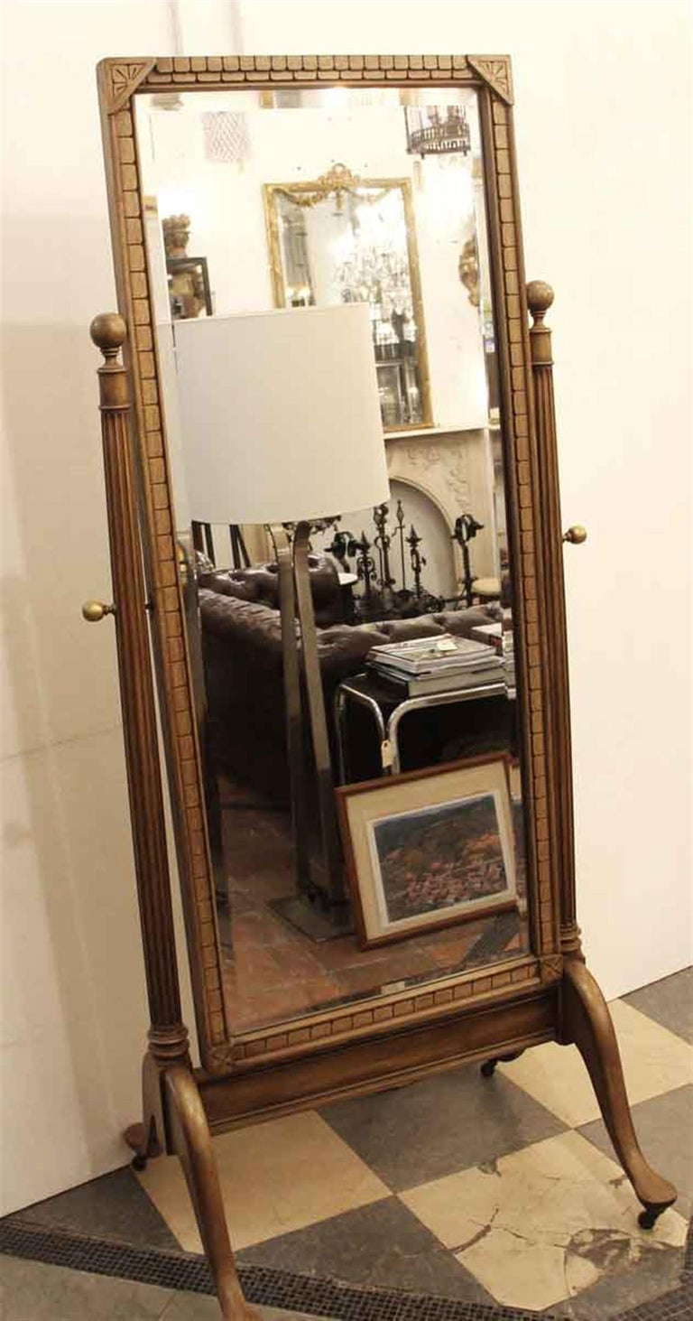 Medium wood tone cheval mirror made of fruitwood with carved details in the Eastlake manner. The decoration is geometric with floral corners with fluted column sides. Brass hardware on sides and furniture wheels. Beveled mirror with slight
