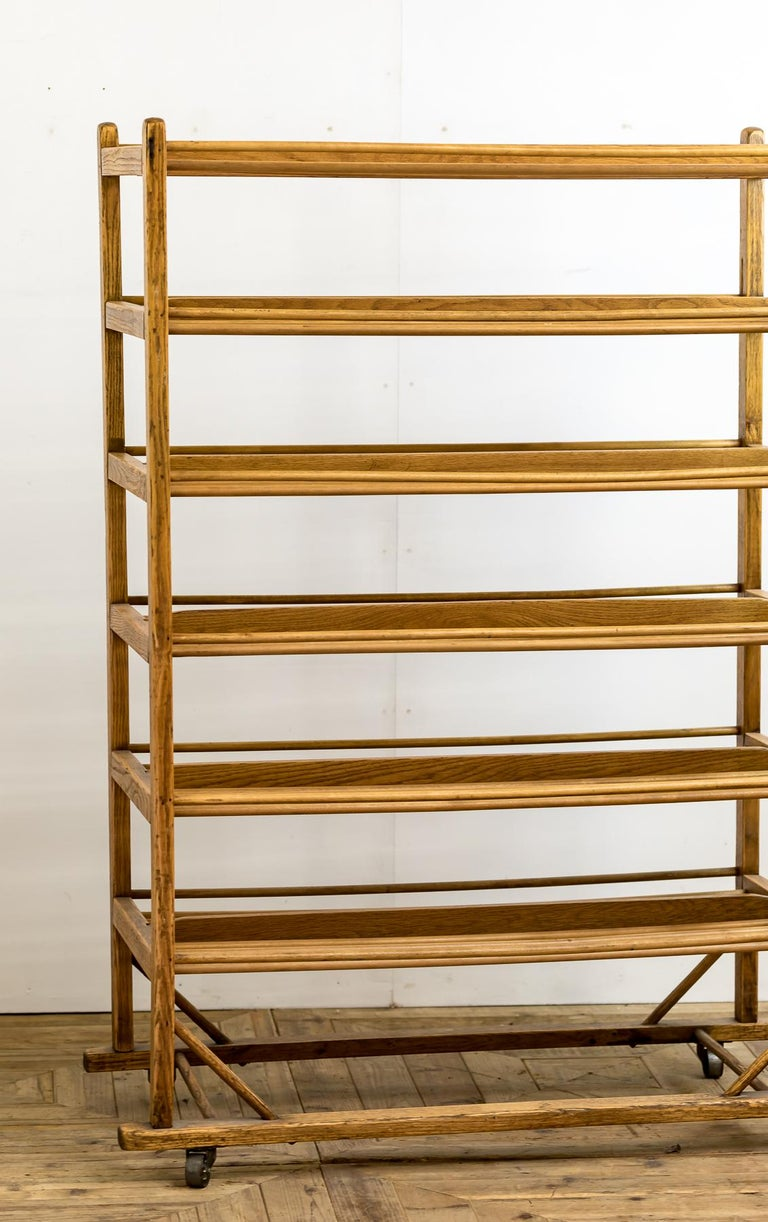 An Industrial bakery cooling rack of traditional form on six tiers and raised on industrial casters.