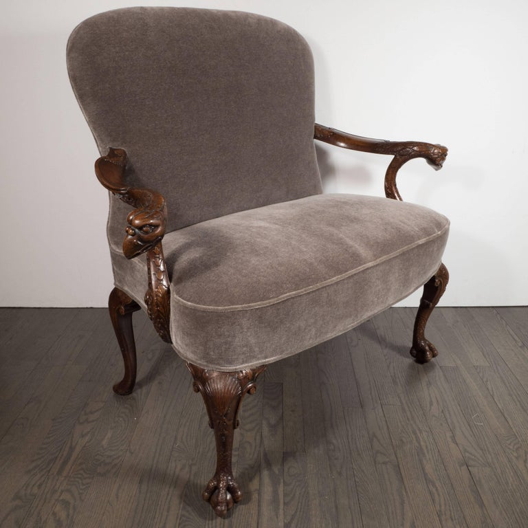 This stunning Edwardian occasional chair was realized in England at the beginning of the 20th century. It is a first-rate example of design from the time and place. It features neoclassical motifs carved throughout, including an aves motif depicting
