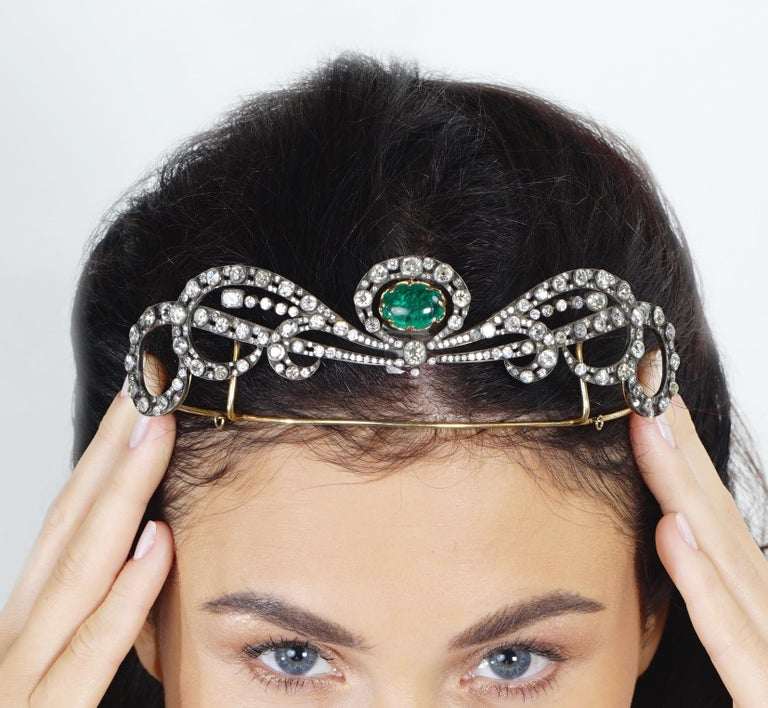 Emerald and diamond tiara, Early 20th century Set throughout with circular-, single-cut and cushion-shaped diamonds, suspending a cabochon emerald drop, length approximately 200mm. The Emerald is Colombian origin.  Diamond total weight: