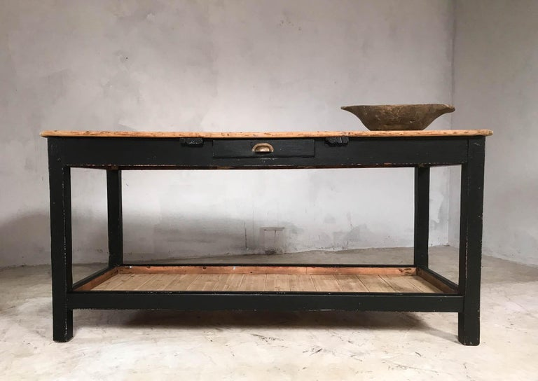 Great looking English pine potting board table in later black paint. Features single drawer in the front with brass cup handle, ample storage on the pine potting boards and beautifully aged original pine top. Attractive piece from front and