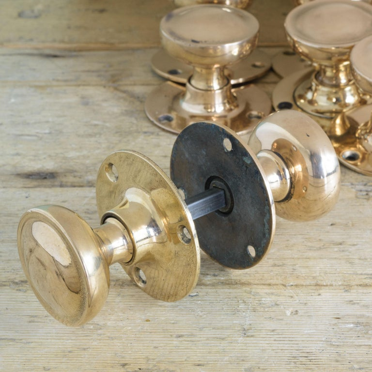 Early 20th century English rose brass door knobs, with circular backplates. Sold as pairs, including spindle.