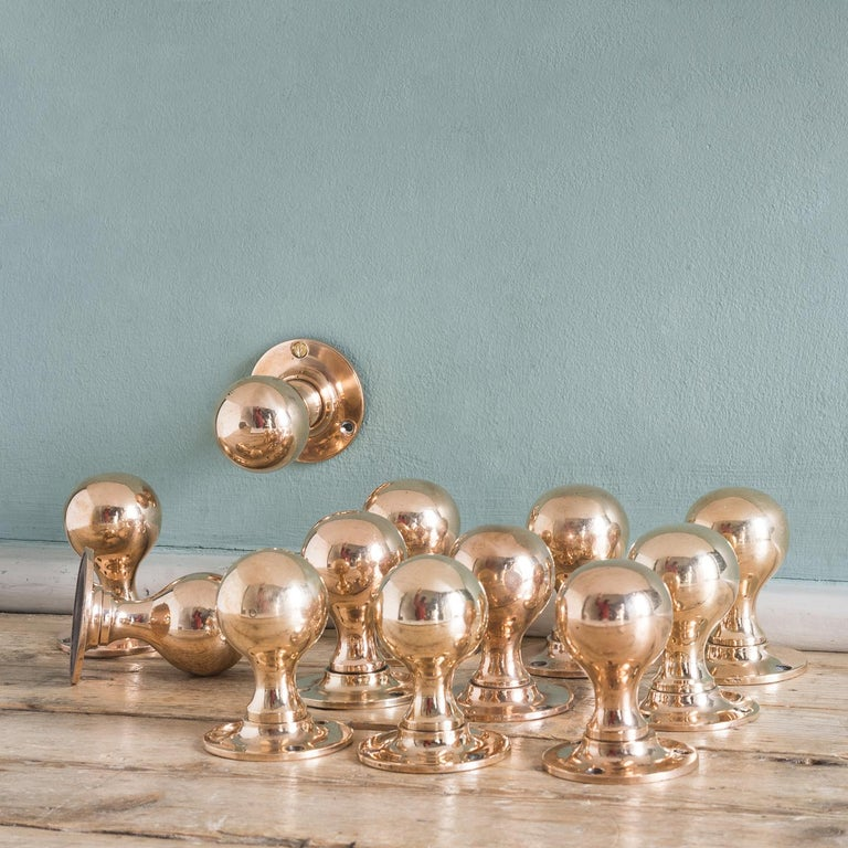 Early 20th century rose brass door knobs, on turned backplates.