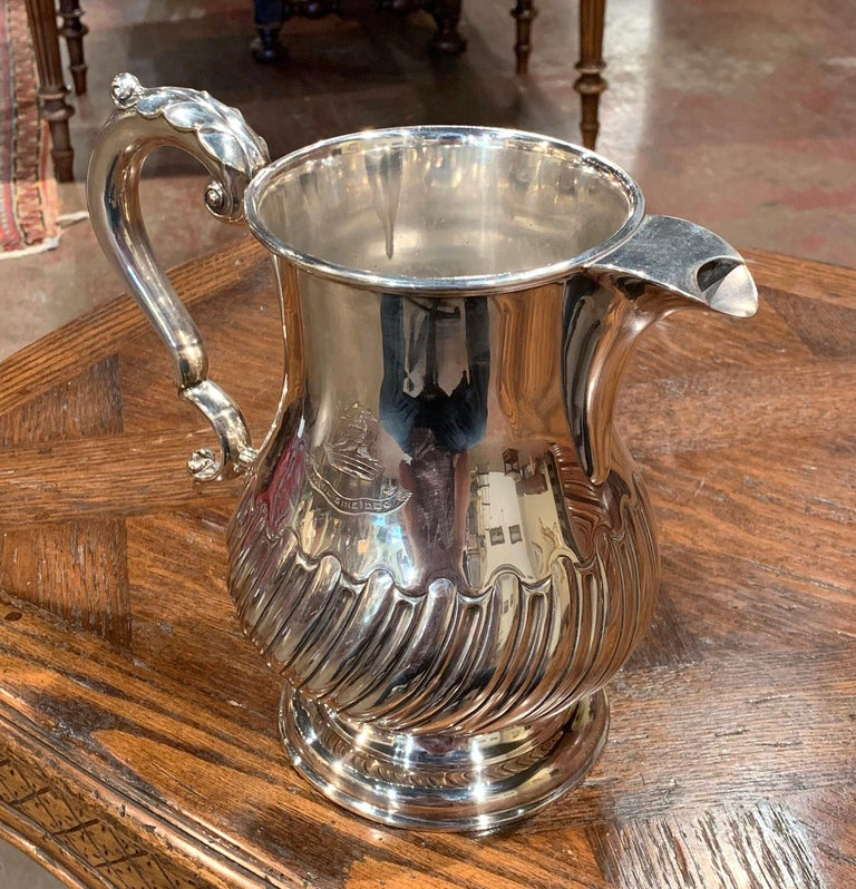Decorate a wet bar with this elegant, antique silver plated pitcher. Crafted in England circa 1920, the traditional, timeless water jug sits on a raised rounded base. The pitcher has a baluster form and a downward sweeping ribbing on the lower half