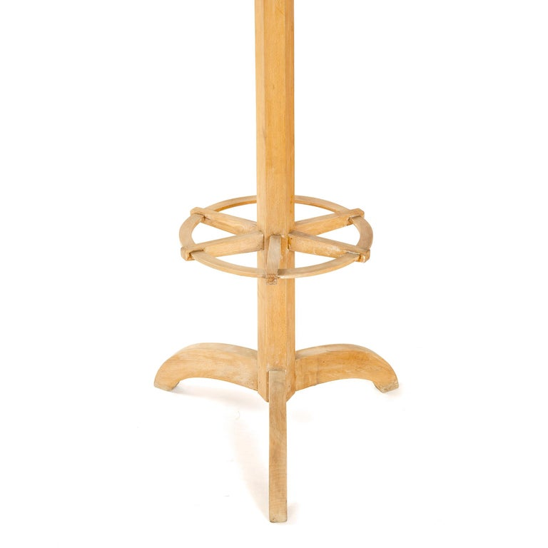 A simple Art Deco coat tree made from solid bleached mahogany with a rotating top.