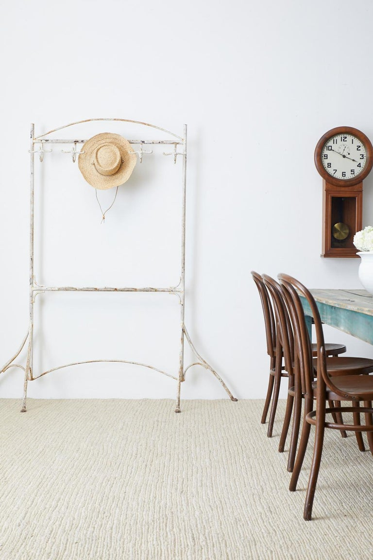 Large early 20th century French Art Nouveau painted iron coat and umbrella rack stand. Features a large wrought iron handcrafted frame with five coat or hat hangers that look like figures with outstretched arms. The middle support has five loops for