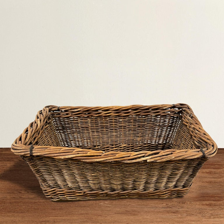 A charming early 20th century French vineyard basket hand-woven from reeds with a heavy rim, rope handles, and wooden slat bottom. Perfect for laundry, or filled with throw pillows and blankets in your family room.