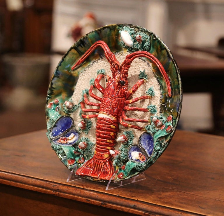 Decorate a wall with this colorful antique hand painted Majolica decorative platter; crafted in Brittany, France, circa 1930, the ceramic plate is sculpted in high relief and decorated with a centre lobster and embellished with clams, mussels,