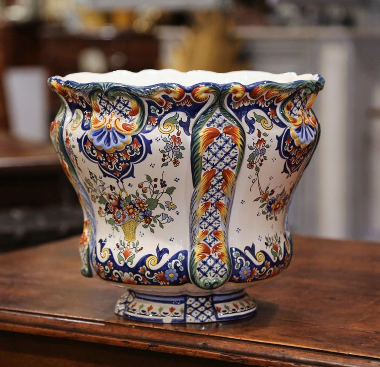This elegant, antique ceramic cachepot was crafted in Normandy, France, circa 1920. Round in shape, the Classic, colorful planter has a curly, scalloped rim. The large, deep porcelain planter features hand painted floral decor in a blue, orange,