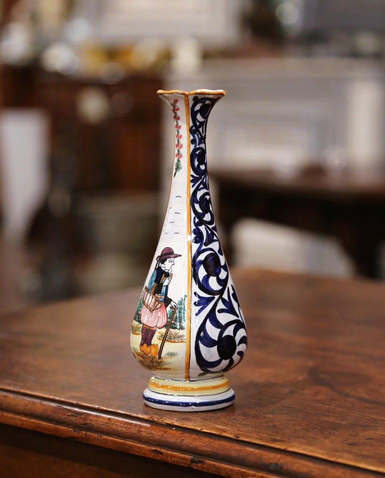 Decorate a shelf with this colorful hand painted flower vase. Created in Brittany, France, circa 1950, the small ceramic vessel is decorated on the front with a Breton man in traditional costumes coming back from the fields, and is embellished with