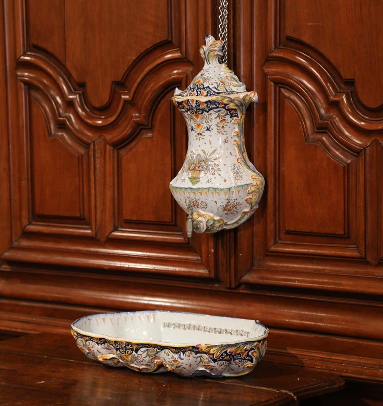 Decorate a wall with this antique ceramic fountain from Normandy. Crafted in Rouen, France, circa 1890, the decorative three-piece set is complete with basin, reservoir with metal spout, and lid. The faience lavabo, shaped as a shell, is hand